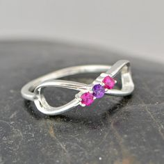 Sterling Silver Infinity Birthstone Ring This ring features an Infinity symbol with your choice Birthstone CZs set in sterling silver. You