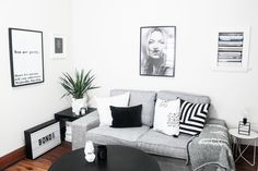 A monochromatic living room with a grey couch, typographic wall art, black and white photography and a pot plant in the corner