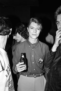 Bowie wears a badge with the photo of him and WIlliam Burroughs taken in 1974 by Terry O'Neill.