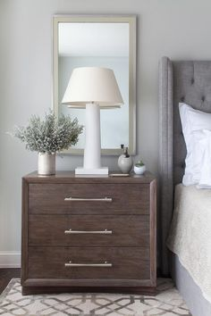 Restful bedroom features a brown 3 drawer nightstand placed on a gray trellis rug and fitted with satin nickel pulls lit by a white lamp positioned in front of a gold and gray mirror mounted to a light gray wall beside a gray linen tufted wingback headboard and bed dressed in cream bedding.