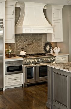 """Gray and White Kitchen with Herringbone subway tile backsplash. Potfiller. Thermador 48"""" range.  Grey island with white cabinets. Microwave drawer. Granite top island"""