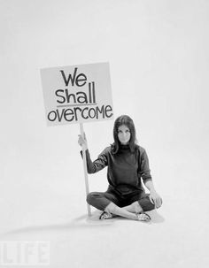 Gloria Steinem is pictured with a we shall over come sign.