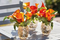 Burnt orange calla lilies are especially charming in small, textured silver vases