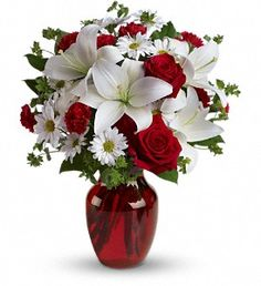 The spirit of love and romance is beautifully captured in this enchanting bouquet. It's the perfect gift for anyone you love.    Red roses and carnations are exquisitely arranged with white asiatic lilies and chrysanthemums in a ruby red glass vase. It's lovely.  (teleflora images used with permission)  A bestseller at $65.00  T128-2A