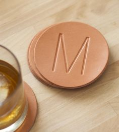 Protect tabletop surfaces with handmade leather coasters, personalized with your initial. The round coasters are cut from thick leather that will age gracefully, eventually earning a patina and softening up with repeated use.