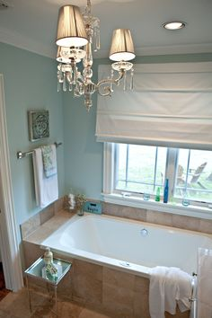 I love the bath tub next to the door, it is space effective and beautiful, Love the chandelier, and the roman shade over the window. Love the blue and white and silver / mirror / crystal feel in the bathroom. House of Turquoise: Beloved Rain washed Beige Tile Bathroom, Rustic Bathroom Mirrors, Bathroom Paint Colors, Brown Bathroom, Coastal Bathrooms, Small Bathroom, Master Bathroom, Bathroom Ideas, Bathroom Lighting