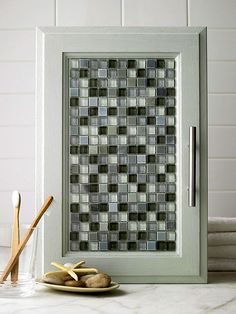Tile Style  THIS I like for the bathroom...  After you've primed and painted your cabinets, add a little sparkle with tile. Lay out and trim mesh-back glass tile to fit the door panel. Apply tile adhesive to the door with a putty knife and adhere the tiles. You don't need to grout the tile, but if you do, be sure the cabinet hinges are strong enough to hold the extra weight of the grout.