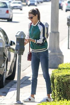 Alessandra Ambrosio wearing Gucci Ace Embroidered Low-Top Sneakers, Lovers + Friends x Revolve the Bomber, Mother Fly Cut Stunner Fray Jeans in Moon Dark and Cartier C De Cartier Mini Bag