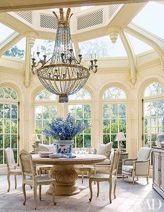 In the sun-drenched conservatory of a Houston home, which serves as a dining area and was renovated by Newberry Campa Architects and decorator Kara Childress, an Italian Empire-style chandelier hangs above a 19th-century Italian marble pedestal table. | archdigest.com