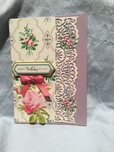 Anna Griffin metallic card with AG lovely layer paper using AG decorative edge die and various AG embellishments