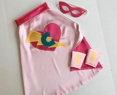 Every little girl wants to be a princess, now she can save herself! Cape is doublesided satin with velcro closure for safety and ease of use for little ones. Mask is made from eco felt fused to satin with elastic strap securely sewn on. Cuffs are made from eco felt and satin and have small