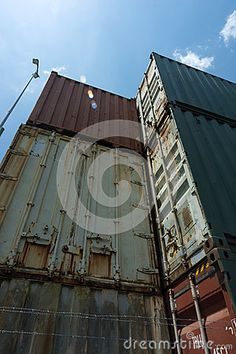 Old and disused shipping containers stacked in a yard, sun flaring over the top. Copyspace.