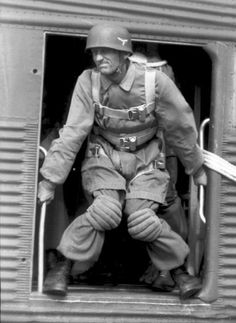 German paratrooper prepares to fly out of the plane during exercises in France,June 1944. By that time, the German paratroop division was already fighting as infantry for three years.The expression of the jumper shows some tension. Four paras have already jumped (count the para lanyards flying out the door of the plane on the right).