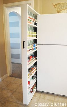 A diy rolling canned food organizer made by Classy Clutter. It uses the small space between the wall and refrigerator.