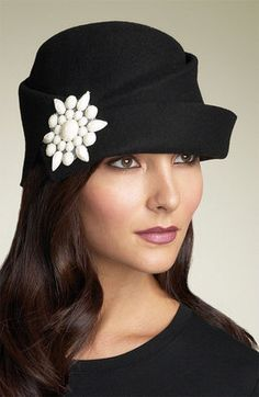 A faceted resin stone adds vintage charm to a pleated cloche with a slightly upturned brim.