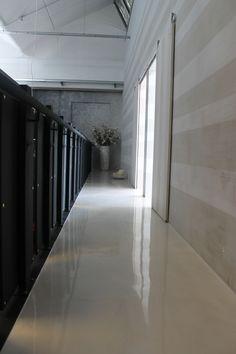 Corridoio realizzato con una superficie in resina lucida per pavimenti a cui è stata abbinata una particolare lavorazione in resina decorativa sulla parete verticale dell'ambiente trattato.