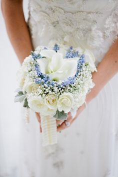 with a pink peony in the center of the blue flowers surrounded by baby's breath and some green flowers and one gardenia.
