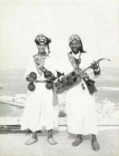 Moroccan Gnawa musicians.One man is holding the Krakeb instruments and the other the Hajhouj or Guembri.