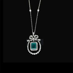 Edwardian emerald and diamond pendant necklace: Deep rich emerald cut emerald weighing approximately 3.25 carats dangles freely from a classic Edwardian set bow and inside a horseshoe shaped frame of high quality, bezel set old mine diamonds. Circa 1900. The diamond chain is relatively new.