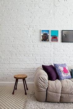Neutro, o sofá em tom claro acomoda as almofadas, uma totalmente roxa e outra com desenho no qual a cor predomina