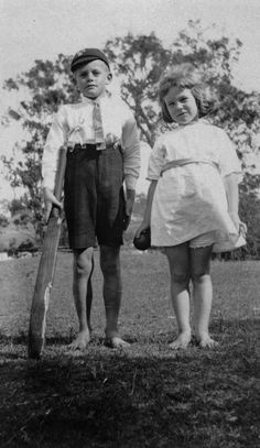Two children playing cricket. Young boy and girl standing on the lawn holding a cricket bat and ball. They are dressed in children's clothes and are not wearing shoes.  Datebetween 1920 and 1930  This image is of Australian origin and is now in the public domain.  File:StateLibQld 1 94472 Two children playing cricket.jpg