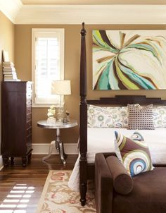 Bold artwork by Buddy Whitlock hangs in the master bedroom and mixes with Sherwin-Williams' Hopsack covering the walls. The bedding is from Vesta's; furniture is from I.O. Metro.