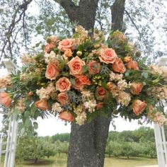 Top of the arch wedding flower spray. Coral roses.