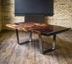 """This 2500-4000 year old redwood burl table top is certified through the Forest Stewardship Council. It is """"square-cut"""" and contains clear, cast resin in each of its natural voids. The table top is paired with the STACKLAB Band Ribbon legs finished in either antique pewter (shown) or brass."""