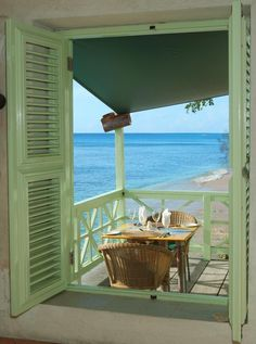 Quaint little sunny breakfast porch with green shutters.
