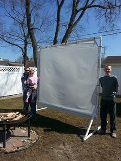 Outdoor movie screen using pvc,  bed sheet with grommets added to it,  and small bungee cords.