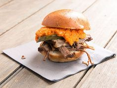 Brisket, braised in stout, bourbon, and soy sauce, is topped with a spicy, gochujang-spiked pimento cheese in these sliders from Kentucky Chef Edward Lee.