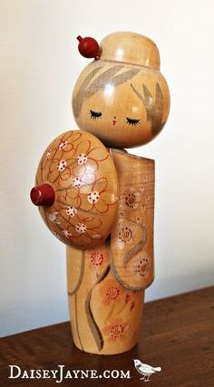 Japanese kokeshi doll. Shes lovely and demure with eyes looking down, almost bashful. Vintage 7.5 kokeshi doll with hair ornament and parasol. Good
