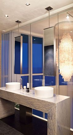 Bathroom furniture and offset mirrors reduce splash against the glass wall beyond