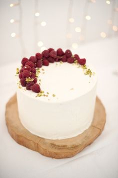 Simple vanilla cake with berries and pistachio sprinkles.