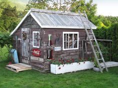 A tin roof tops this rustic backyard shed that features distressed painted siding and vintage metal signs.