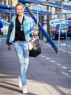 A black t-shirt is paired with a denim jacket, skinny jeans, and Adidas sneakers