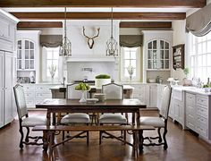 white cabs, dark beams & floors, relaxed gray roman shades, arched glass cabs, table, bench,lights!
