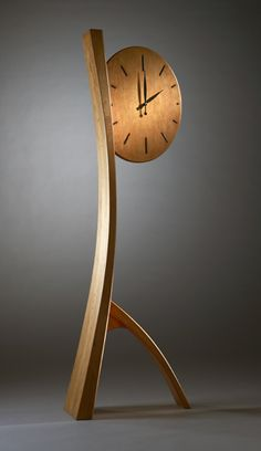 Sweeping curves of thick-skinned black cherry give this wooden floor clock its natural grace and charm. Ebony accents are inlaid into the solid cherry oval clock face. Side view reveals tapered legs. Limited edition of 5. Signed on back. $6600.00
