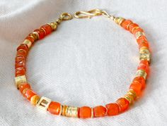 N1417140 | Faceted carnelian cubes, bright as poppies, in a composition with matte 24K vermeil squares, cylinders, and opals, and orange opal accents. Closed with a matte vermeil hook clasp. Length 17 inches. (Can be lengthened upon request for slight up-charge.) $375