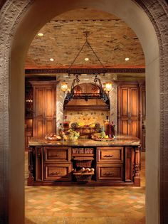 A stone arch frames this kitchen like an Old World masterpiece. In the foreground, a large work island features a mahogany base topped with Verde Fuoco granite. Beyond, the cooking area gleams beneath a hammered-copper hood and a mosaic medallion from Italy.