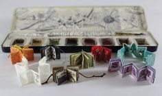 A rainbow of miniature handmade accordion books housed in a watercolor paint box, created by Lesley Patterson-Marx and displayed at the 2012 Handmade and Bound Festival in Nashville.