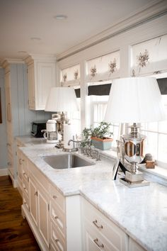 Ok, j'adore the cabinets, counters, shades, and shiny bits. Lamps in the kitchen...I could be persuaded.  Plugged in appliances 6 inches from the sink? Not so much. (Oh, and it might be hard to see, but at least THESE lamps have cords!)