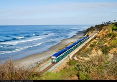 Southbound on Amtrak's Pacific Surfline, a San Diego Coaster has just made its daily station stop at Solana Beach, now enroute to Sorrento Valley and Old Town in San Diego through the wealthy community of Del Mar. A true Southern California scene!