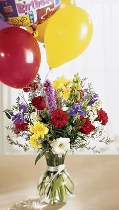 The best and brightest birthday bouquet.  1 mylar balloon and 4 multi-colored latex balloons are tied to a glass vase full of brilliantly colored flowers.  Arrangement includes red roses, blue iris, white lisianthus, purple liatris and more. Colorburst Birthday Balloons and Flowers - $105.00 Available online for worldwide delivery at Brant Florist.