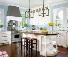 White cabinets, pale blue walls, and an embellished island are chic and elegant. The cherrywood top on the island, gray range hood, and dark floors anchor the spacious room./