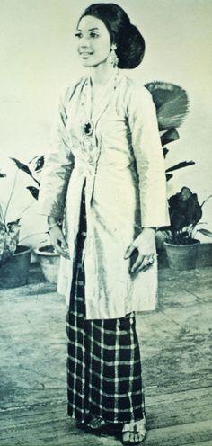 Baju Kebaya Labuh Salah satu pakaian tertua dan masih lagi dipakai sehingga hari ini. Pakaian ini merupakan baju labuh yang berbelah sepanjang bahagian depannya dan disemat dengan tiga biji kerongsang. Baju kebaya dipadankan dengan kain sarung yang dilengkapkan dipinggang dengan meletakkan kepala kain di depan. Traditional Fashion, Traditional Dresses, Indonesian Kebaya, Dutch East Indies, Asian Design, Historical Clothing, Culture, History, Image