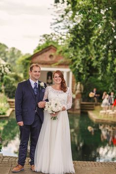 The bride wore a Watters wedding dress for her wedding at The Great Barn at Micklefield Hall in Hertfordshire. The bridesmaids wore navy blue. Photography by Benjamin Stuart.
