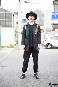 This is Shin, a stylish 18-year-old guy. He is wearing a paint-splattered sweatshirt and color blocked jacket from the Japanese brand Soe with pants from Ganryu Comme Des Garcons. We also noticed his hat, tattoo bracelet and rings, black nails, gray Nike Air Jordan backpack, polka dot socks and black oxfords.