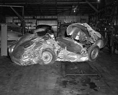 """The wrecked remains of James Dean's Porsche 550 Spyder """"Little Bastard"""" lie in the garage of a repair shop in Paso Robles, California. The car that hit him is in the back center. The 24-year-old film star was killed on the evening of September 30th when his car collided with a college student's automobile at an intersection 28 miles east of Paso Robles."""