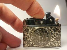 Vintage 1960s push button CORONET automatic lighter with engraved silver overlay depicting the Aztec Calendar on one side and the Mexico eagle with